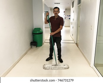 Asian male janitor mopping floor in hallway interior office building with trash bin. Worker cleaner service in school.