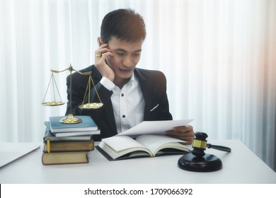 Asian male lawyer reading documents in his home office.