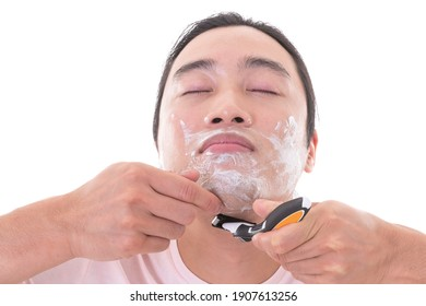 Asian male model shave his beard with razorblade isolated on white background