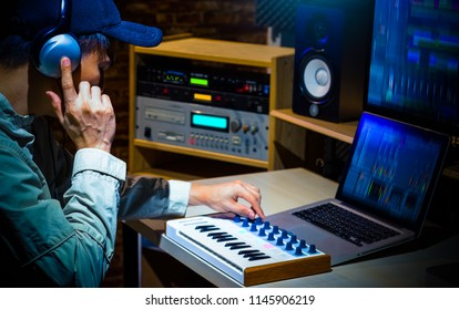 asian male music producer composing a song in digital sound studio