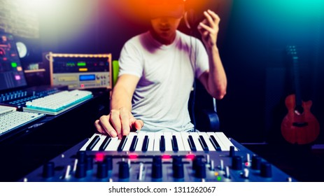 asian male music producer, dj making electronic dance music in sound studio