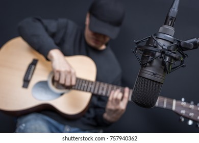 asian male musician recording acoustic guitar in sound studio