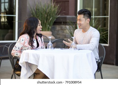 Asian male on an outdoor date with a black female.  They are sitting in a street cafe or coffee shop for brunch or lunch.  The image depicts diversity in relationships.