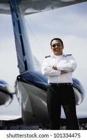 Asian male pilot standing at tail of private airplane