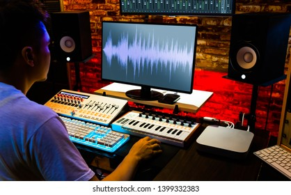 asian male producer recording, editing, mixing sound on computer in home studio, music production concept
