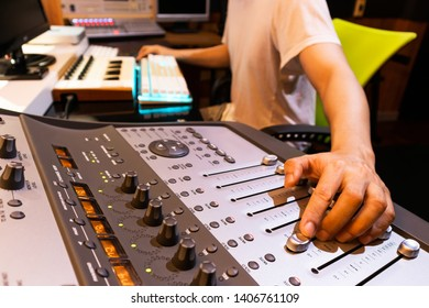 asian male professional producer mixing audio tracks on digital sound mixer in home studio. music production concept