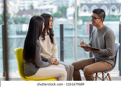 Asian male professional psychologist doctor giving the consult to Lesbian lovers patients which have relationship problem in modern living room of house or hospital exam room, Mental health Concept