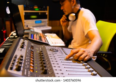 asian male professional sound engineer working in recording, broadcasting, editing studio