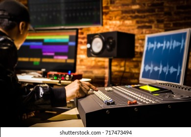 asian male professional sound engineer working in digital recording, broadcasting, editing studio. focus on mixer fader