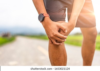 asian male runner in pain on injury at the knee the leg on a road exercising or practicing for a marathon race, wearing smartwatch and trainers with mountain and cloudy sunset sky in the background