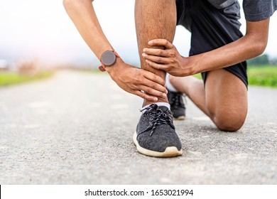 asian male runner in pain on injury at the ankle the leg on a road exercising or practicing for a marathon race, wearing smartwatch and trainers with mountain and cloudy sunset sky in the background