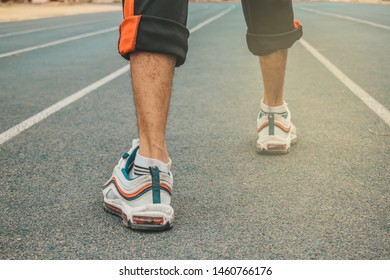Asian male runnes jogging on city streets