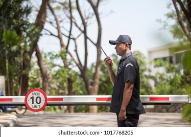 Asian Male Security Guard Talking a portable wireless transceiver in village  entrance . Security guard opening The entrance to the village door. Speed 10 limit in area,copy space.