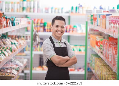 asian male shopkeeper standing in front of the groceries store
