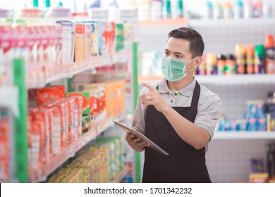 asian male shopkeeper working in a grocery store
