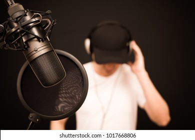 asian male singer listening backing track before singing a song in recording studio, focus on microphone