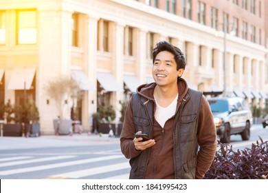 Asiatische Männchen lächeln und freut sich, während er sein Handy hält - App Based Transport - City - Daytime