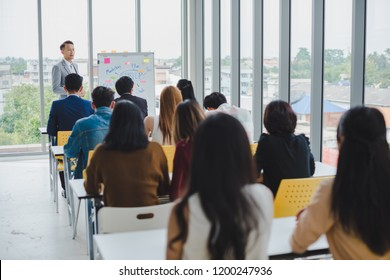 Asian male speaker is speaking at seminars and workshops to the people in the meeting.
