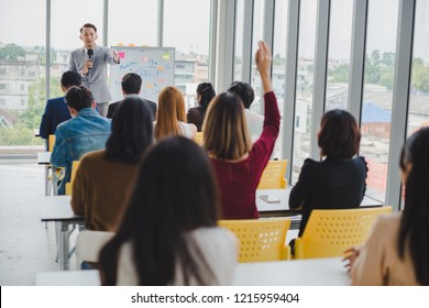 Asian male speaker is speaking at seminars and workshops to the people in the meeting. Participants are raising their hands to ask questions.