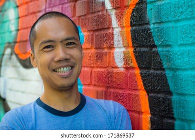 An Asian male stands against colorful graffiti wall in an urban environment, with a big smile