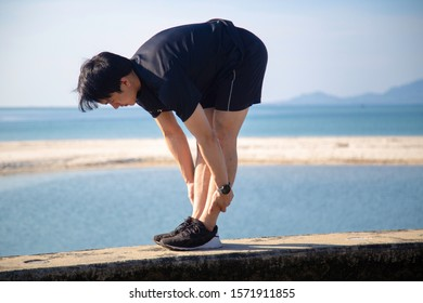 Asian male is stretching before doing work out ,jogging at seaside in the moring with beautiful sea view