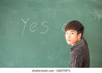 asian male student in front of blackboard with 'Yes ' or 'no' in blackboard