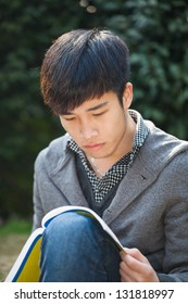 asian male student studying in the park