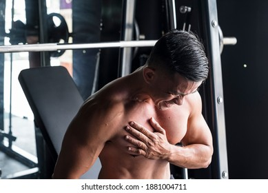 An asian male suffers a torn pectoral muscle while doing heavy incline bench presses on a Smith Machine at a gym or fitness center. A common workout injury