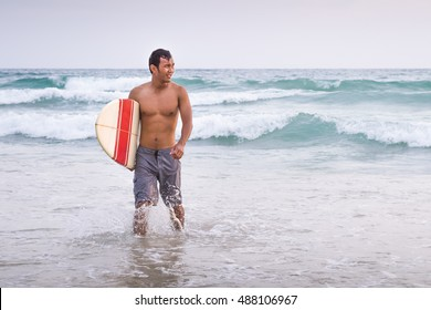 Asian male surfer walking to the beach after done surfing session