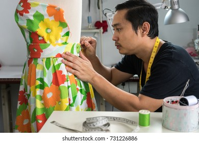 Asian male tailor be used needle pinning fabric attach to dummy