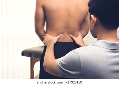 Asian male therapist in clinic giving massage on lower back of  patient treating pain from office syndrome  - physical therapy concept