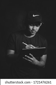 Asian Male using iPad tablet and pencil to edit photo. Man wearing cap.