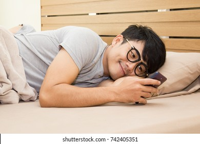 Asian male using smartphone on the bed in the midnight.