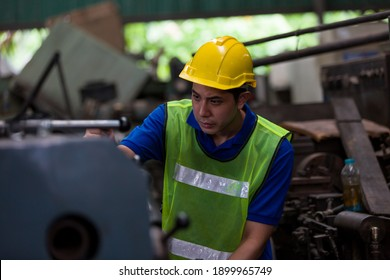Asian male worker working with lathe machine in factory. Male engineer worker checking, repair or maintenance machine in factory. Male worker wearing safety uniform, helmet and gloves at work factory