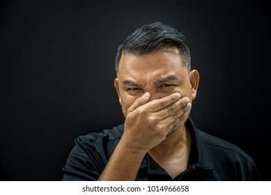 Asian man 40s have a short hair in black polo shirt make gestures off their nose and mouth to prevent unpleasant smell from the pollution or stench smell on black background dark style