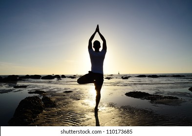 Asian man acts yoga on the beach in the morning silhouetted against sunlight.