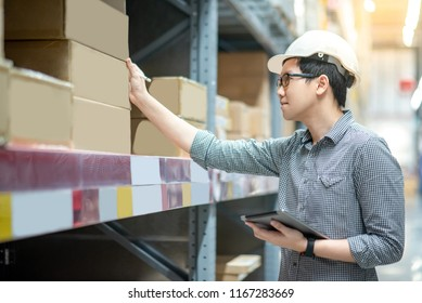 Asian man assistant worker wearing safety helmet and eyeglasses doing stocktaking of product in cardboard box on shelves in warehouse by using digital tablet and pen. Factory physical inventory count