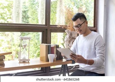 Asiatischer Mann mit attraktivem Lächeln, während Sie Tablet im Café, 20-30 Jahre alt.