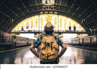Asiatische Mann Backpackung Anfahrt auf Bahnhofshintergrund, Reise auf Urlaubskonzept .