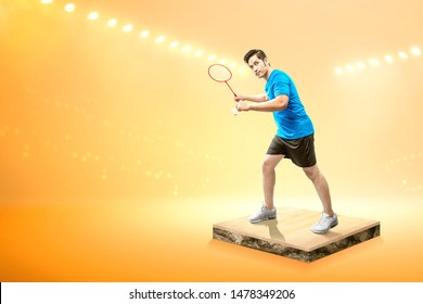 Asian man with badminton racket holding shuttlecock and ready in serve position on the badminton court with spotlights