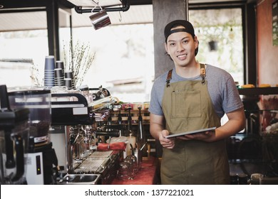 asian man barista holding tablet for checking order from customer on coffee cafe.