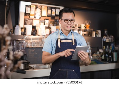 Asian man barista smiling with tablet in her hand,Female employees are taking orders from online customers
