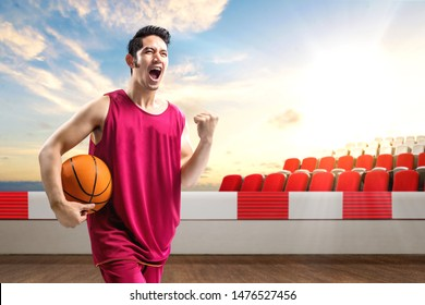 Asian man basketball player holding the ball with an excited expression on the outdoor basketball court