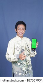 asian man with batik clothes and pointing at green screen cellphone