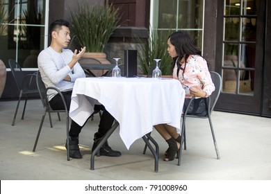 Asian man and black female couple fighting or incompatible while on an outdoor cafe date.  They look unhappy in the restaurant. The image depicts relationships and rejection.