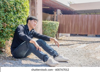 An Asian man in black shirt and denims sitting on the pebble ground under the daylight.