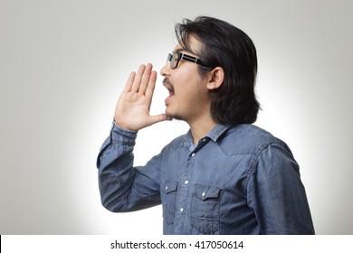 The asian man in blue denim shirt is shouting.