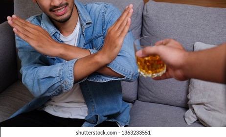 Asian man in blue jean jacket refuses to drink a alcohol by cross hand. Male alcoholism concept. Treatment of alcohol addiction. Quit booze and alcoholism