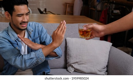Asian man in blue jean jacket refuses say no and avoid to drink a alcohol whiskey by stopping hand sign male alcoholism concept treatment of alcohol addiction quit booze