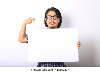 The asian man in the blue plaid shirt is pointing on white board.
